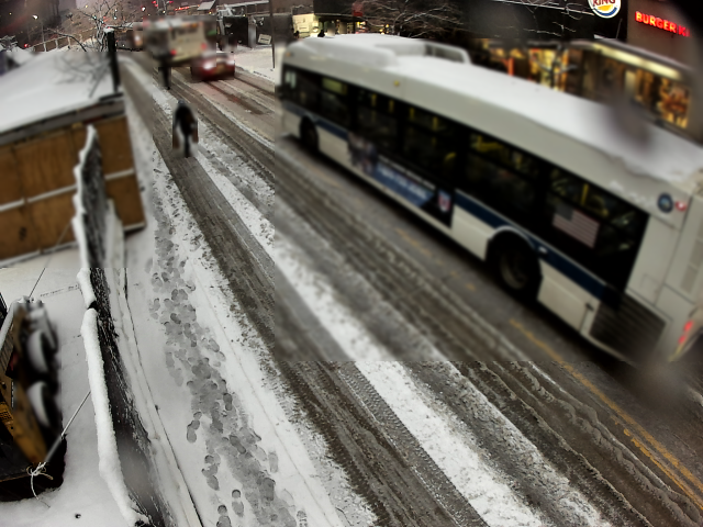 Snowy city street (Fulton Mall) with bus in one lane and pedestrian walking in other traffic lane.