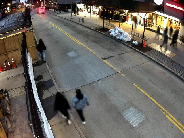 Two pedestrians walking in street (Fulton Mall) to avoid scaffolding